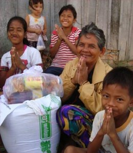 Grandmother and her grandchildren, grateful to get flooding relief in Cambodia.