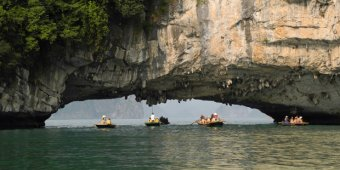 Travelers canoe under a stone arch in Bai Tu longer Bay on April 19, 2015 near Ha longer City, Vietnam. Air NZ begins flying to Ho Chi Minh City from Summer next year. Picture / Getty graphics